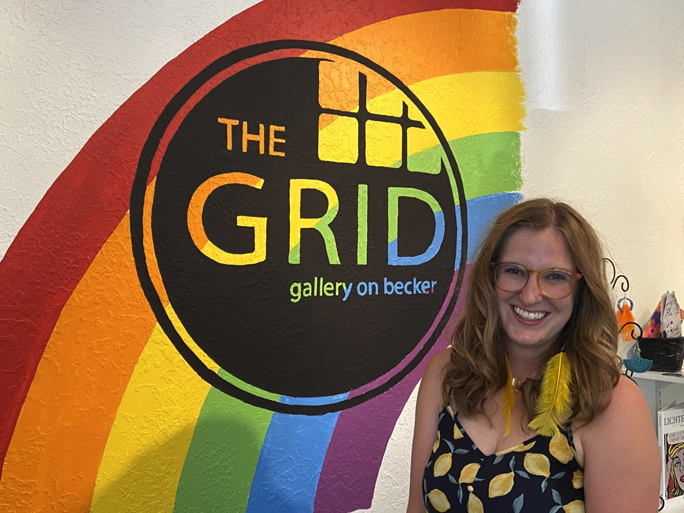 Megan Morgan-COrdova GRID Gallery owner stands in from of a logo for the gallery with a rainbow behind it