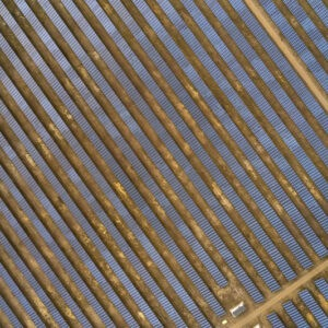 Solar panels in a large cluster forming solar power plant, top down aerial view